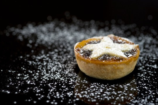 Festive mince pie with icing sugar on black background.