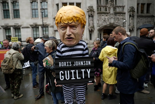 A person dressed as a caricature of British Prime Minister Boris Johnson in a prison uniform stands outside the Supreme Court in London, Tuesday, Sept. 24, 2019 after it made it's decision on the legality of Johnson's five-week suspension of Parliament. In a setback for Johnson, Britain's Supreme Court has ruled that the suspension of Parliament was illegal. The ruling Tuesday is a major blow to the prime minister who had suspended Parliament for five weeks, claiming it was a routine closure. (AP Photo/Matt Dunham)