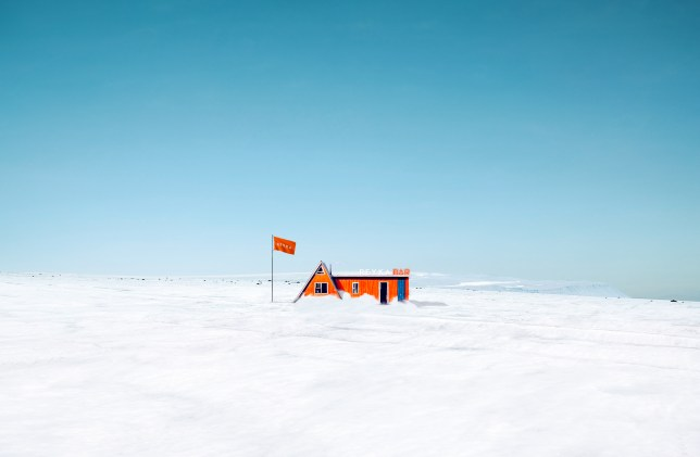 A small orange house with a sign that says bar, along with a flag flying in the wind outside on top of a glacier in Iceland, with nothing but snow around