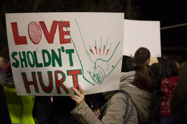 A woman holds a sign reading Love Shouldn't Hurt