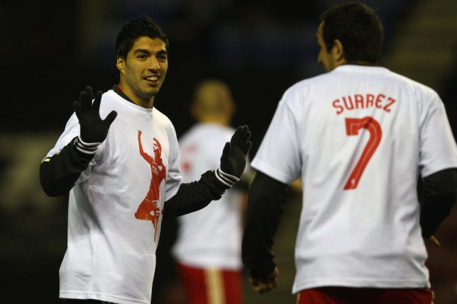WIGAN, ENGLAND - DECEMBER 21: Luis Suarez (L) looks towards Jose Enrique (R) of Liverpool as the teams warm up ahead of the Barclays Premier League match between Wigan Athletic and Liverpool at the DW Stadium on December 21, 2011 in Wigan, England. (Photo by Michael Steele/Getty Images)
