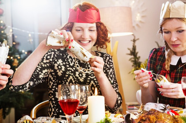 Two women sat at a Christmas dinner opening crackers