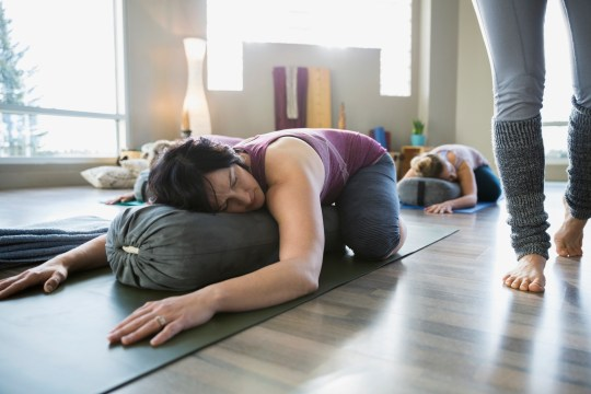 Woman doing restorative yoga in a studio, stretching across a pillow with the instructor's legs seen walking beside her