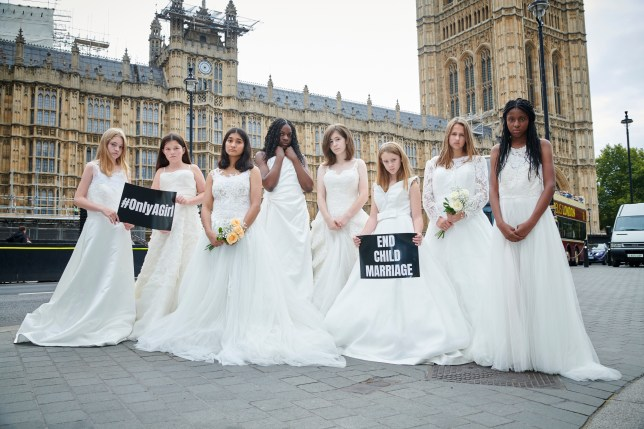 Young girls dressed in wedding dresses and standing in front of the Houses of Parliament
