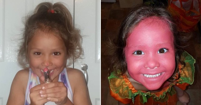 Little girl with pink lipstick smeared on