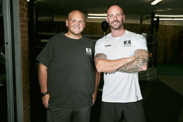 """Darren McClintock, 27 with trainer, Mike Hind. A man is literally half the person he used to be after losing a whopping TWENTY STONE in the space of just 12 months. See SWNS story SWLEweight. Darren 'Dibsy' McClintock embarked on the epic weight loss journey last October after doctors warned he was """"eating himself to death"""". In the months since Dibsy has lost the equivalent amount of weight as hulking Hollywood superstar Arnold Schwarzenegger. This time last year he couldn't walk up the stairs, wear a seat belt, fit in the bath or travel on public transport. But since turning his life around the 28-year-old has competed in the Great North Run, fought in a charity boxing match and climbed Ben Nevis. Six weeks ago he went 'official' with a new girlfriend, who he met after receiving some messages of support over Facebook."""
