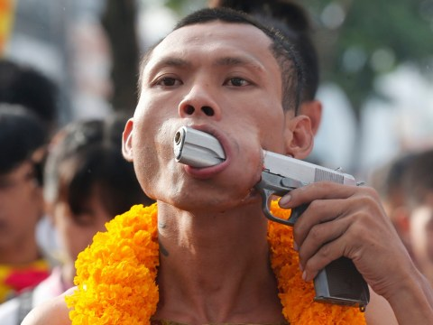 Devotee pierces his face with a gun at vegetarian festival