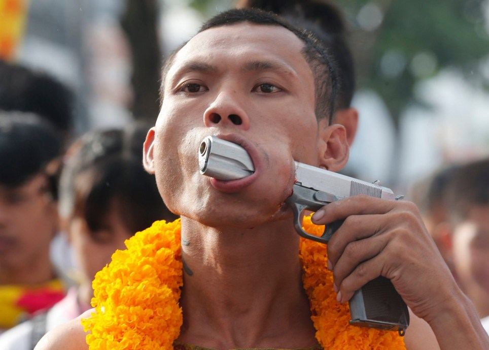 Devotee pierces his face with a gun at vegetarian festival in Thailand