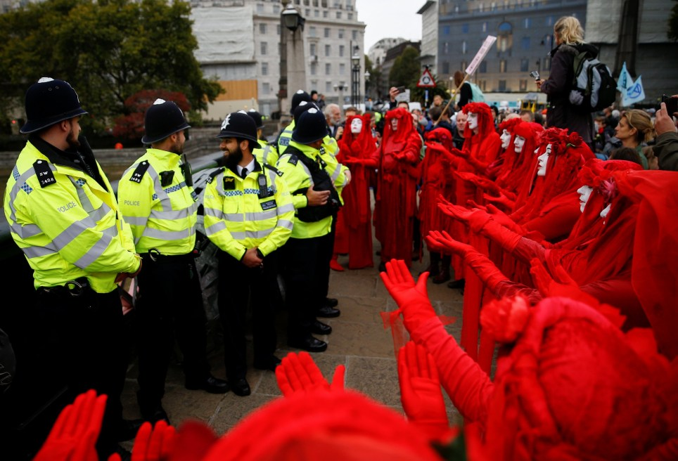 """The Red Brigade"" activists gesture in front of police officers during the Extinction Rebellion protest in London, Britain October 7, 2019. REUTERS/Henry Nicholls"