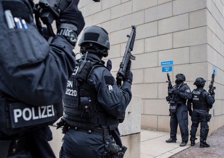 Police officers secure a synagogue in Halle, Germany, Wednesday, Oct. 9, 2019. One or more gunmen fired several shots on Wednesday in the German city of Halle. Police say a person has been arrested after a shooting that left two people dead. (Robert Michael/dpa via AP)