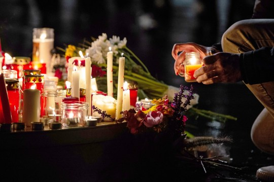 A man lights a candle at a vigil in Halle an der Saale, eastern Germany