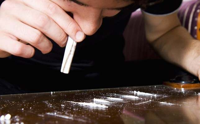 Young man snorting cocaine through rolled up banknote (Photo by Universal Images Group via Getty Images)