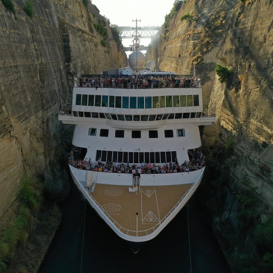 The cruise liner passes through the small Greek canal