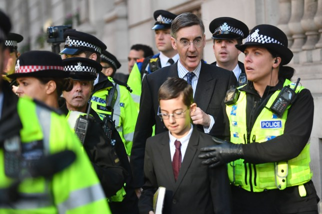 Leader of the House of Commons Jacob Rees-Mogg with his son Peter Theodore Alphege, as they are escorted to his house by police officers during an anti-Brexit, Let Us Be Heard rally in Parliament Square, London, after it was announced that the Letwin amendment, which seeks to avoid a no-deal Brexit on October 31, has been accepted. PA Photo. Picture date: Saturday October 19, 2019. See PA story POLITICS Brexit. Photo credit should read: Jacob King/PA Wire