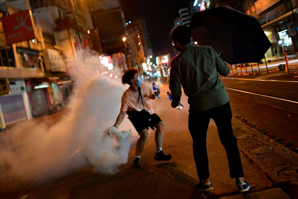 A pro-democracy protester throws back a tear gas canister fired by riot police in Yuen Long district of Hong Kong on October 21, 2019, after a scheduled pro-democracy gathering to mark the three-month anniversary of the triad attack that took place in the Yuen Long train station. (Photo by Anthony WALLACE / AFP) (Photo by ANTHONY WALLACE/AFP via Getty Images)