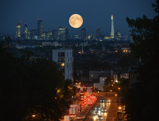 The super moon rises over the City of London skyline