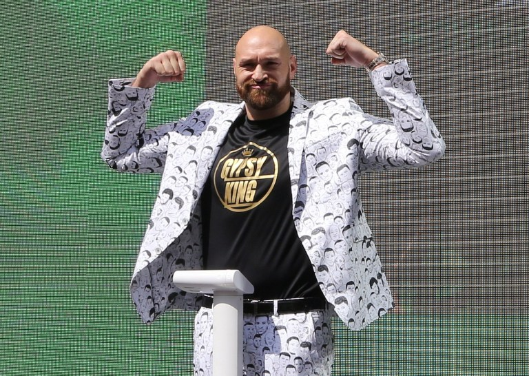 Tyson Fury flexes as he steps on the scales before his WWE debut