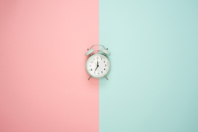 An alarm clock against a colourful background.