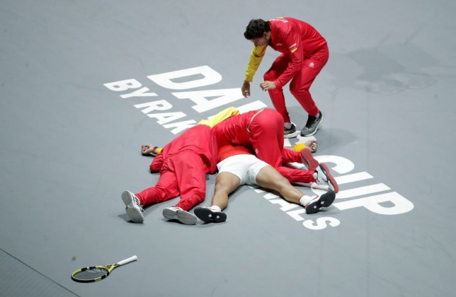 Rafael Nadal is mobbed by his Spain team-mates after they win the Davis Cup