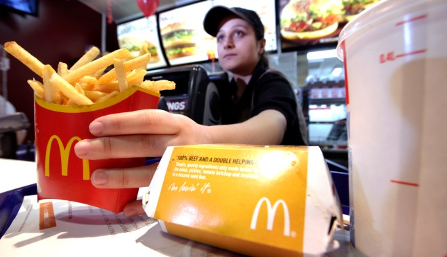 A McDonald's worker handing over fries to a customer
