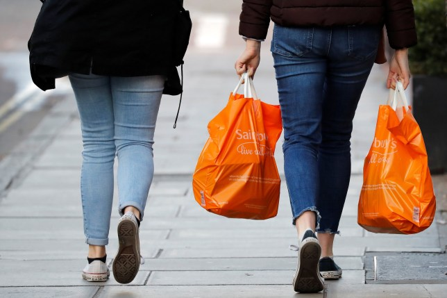 Shoppers carry their purchases in orange plastic Sainsbury's supermarket store shopping bags as they walk in London on November 7, 2019. - Sainsbury's plunged into a net loss in the first half on costly store closures, the British supermarket said Thursday -- and after it recently failed to merge with Walmart-owned Asda. Sainsbury's chalked up a loss after tax of ??38 million ($49 million, 44 million euros) in the 28 weeks to September 21, the retailer said in a trading update. (Photo by Tolga AKMEN / AFP) (Photo by TOLGA AKMEN/AFP via Getty Images)