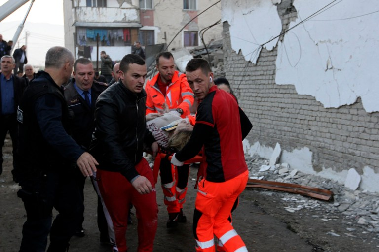 Rescuers carry an injured woman after a magnitude 6.4 earthquake in Thumane, western Albania, Tuesday, Nov. 26, 2019. Rescue crews used excavators to search for survivors trapped in toppled apartment buildings after a powerful pre-dawn earthquake in Albania killed at least six people and injured more than 300. (AP Photo/Hektor Pustina)
