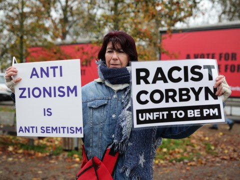 Protesters hold 'Corbyn is racist' signs outside Labour race event