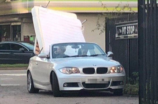 """A BMW with a mattress and bed frame upright on the back seat, which was stopped by police in Colchester, Essex. See SWNS copy SWCAbed: A BMW convertible was stopped by police after it was spotted being used to transport a double bed. A picture posted online by Essex Police shows the roof down and a mattress and bed frame upright on the back seat. Officers had been on patrol in Colchester Road between Colchester and Basildon and wrote about the """"insecure load"""" on Twitter."""