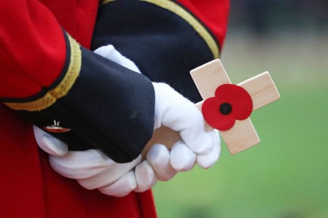 A veteran holds a cross bearing a poppy