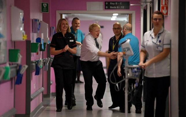 Britain's Prime Minister Boris Johnson greets staff as he walks with Chief Nurse Suzanne Banks and Divisional Head of Nursing Robin Binks during a general election campaign visit to King's Mill NHS Hospital in Mansfield, Britain November 8, 2019. Daniel Leal-Olivas/Pool via REUTERS