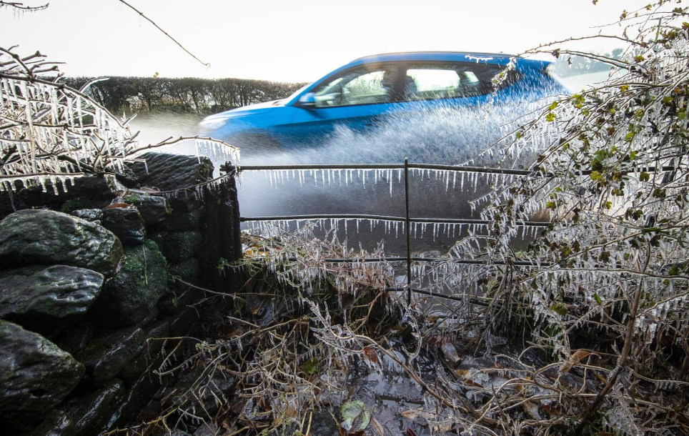 After overnight temperatures plummet below zero, a car splashes through roadside puddles helping to add ice to an already frozen hedgerow and five bar gate in Calwich near Ashbourne Derbyshire