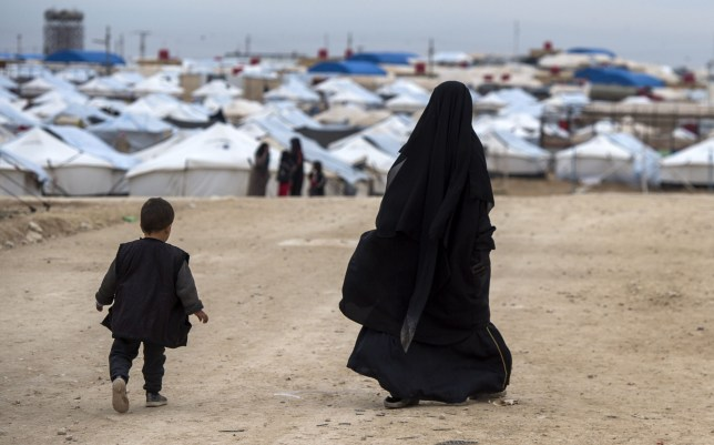 TOPSHOT - A displaced Syrian woman and a child walk toward tents at the Internally Displaced Persons (IDP) camp of al-Hol in al-Hasakeh governorate in northeastern Syria,on February 7, 2019. (Photo by FADEL SENNA / AFP) (Photo credit should read FADEL SENNA/AFP via Getty Images)