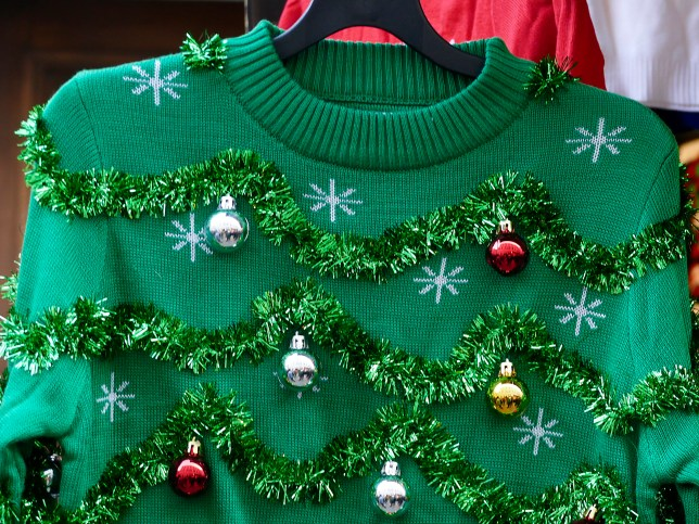 An ugly green Christmas jumper with green tinsel and small baubles in silver, red and gold
