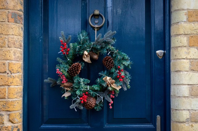 A Christmas wreath hangs on the front door of a house