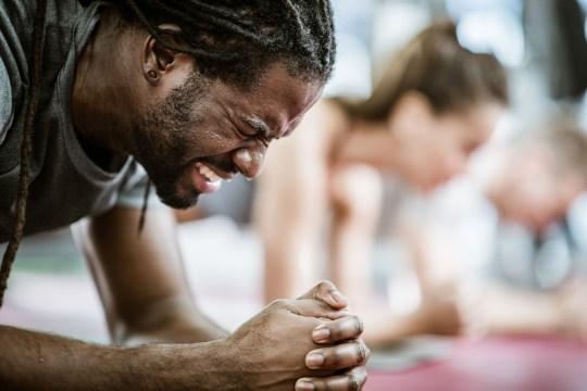 Athlète afro-américain en sueur faisant un effort alors qu'il est en position de planche dans un centre de bien-être.