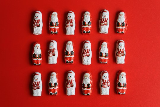 Rows of foil covered chocolate Father Christmas and snowmen on a red background.