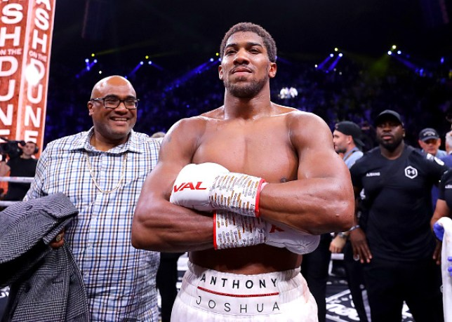 Boxer Anthony Joshua poses after winning back his heavyweight titles