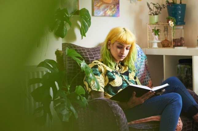 woman sitting in a room filled with indoor plants
