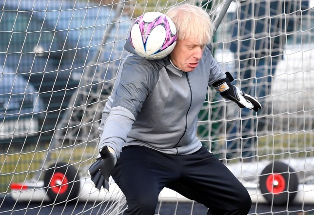 Britain's Prime Minister Boris Johnson tries to save a shot during a warm up before a girls football match while on the campaign trail in Cheadle Hulme, northwest England on December 7, 2019. - Britain will go to the polls on December 12, 2019 to vote in a pre-Christmas general election. (Photo by TOBY MELVILLE / POOL / AFP) (Photo by TOBY MELVILLE/POOL/AFP via Getty Images)