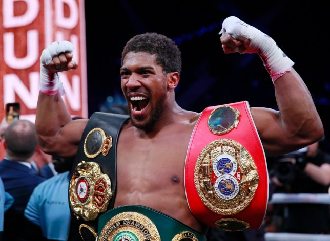 Anthony Joshua flexes with his heavyweight titles