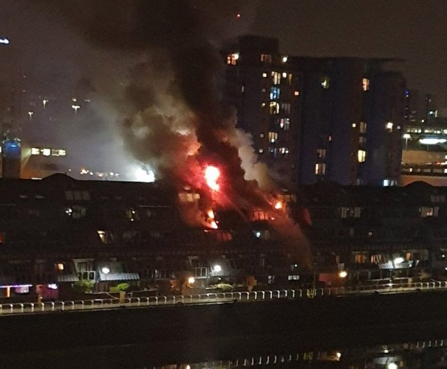Flames can be seen shooting through the roof of the three-storey building (Picture: FrankP00259084)