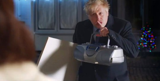 Handout video grab taken from the twitter feed of Prime Minister Boris Johnson of himself in a pop-culture inspired campaign video ahead of the General Election. PA Photo. Issue date: Monday December 9, 2019. In video posted by Boris Johnson on Monday evening, the Prime Minister emulates an scene from Love Actually as he approaches an apathetic voter with a series of placards on her doorstep. See PA story POLITICS Election. Photo credit should read: BorisJohnson/Twitter/PA Wire NOTE TO EDITORS: This handout photo may only be used in for editorial reporting purposes for the contemporaneous illustration of events, things or the people in the image or facts mentioned in the caption. Reuse of the picture may require further permission from the copyright holder.