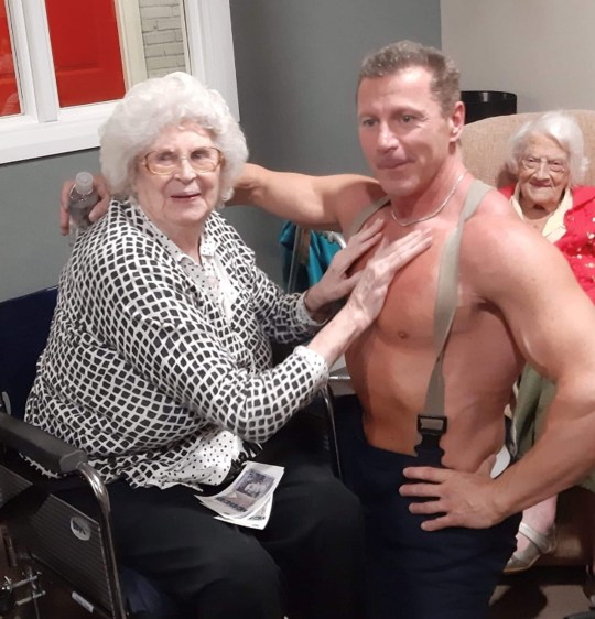 """Undated handout photo issued by Care UK of Glastonbury Court care home resident Joan with a stripper after her wish was granted by the management. PA Photo. Issue date: Thursday December 12, 2019. The 89-year-old resident, who gave her name only as Joan, made the request for a visit from an attractive man with """"a large chest and big biceps"""" through her care home's wishing tree initiative. She and her 84-year-old friend were delighted when a stripper dressed as a fireman arrived at the care home in Bury St Edmunds, Suffolk. See PA story SOCIAL Stripper. Photo credit should read: Care UK/PA Wire NOTE TO EDITORS: This handout photo may only be used in for editorial reporting purposes for the contemporaneous illustration of events, things or the people in the image or facts mentioned in the caption. Reuse of the picture may require further permission from the copyright holder."""