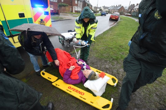 A 79-year-old woman was left lying in the pouring rain after waiting more than two hours for an ambulance. Raymond Bell said his wife, Anne Bell, was left in the cold outside Margaret Thompson Medical Centre, in Speke, Liverpool, after she suffered a fall on Thursday afternoon [Dec 12]. Caption: Paramedics treating Anne Bell outside Margaret Thompson Medical Centre in Speke, Liverpool, on December 12, 2019