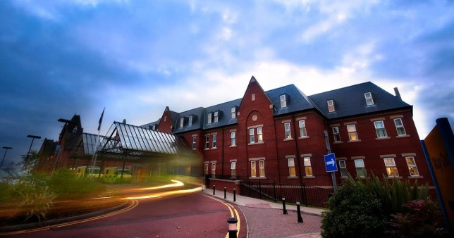 A woman has died after being hit by a car outside Wigan Infirmary. The driver, police say, failed to stop at the scene. caption: Royal Albert Edward Infirmary in Wigan