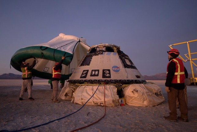 Boeing, NASA, and U.S. Army personnel work around the Boeing Starliner spacecraft shortly after it landed in White Sands, N.M., Sunday, Dec. 22, 2019. Boeing safely landed its crew capsule in the New Mexico desert Sunday after an aborted flight to the International Space Station that threatened to set back the company's effort to launch astronauts for NASA next year. (Bill Ingalls/NASA via AP)