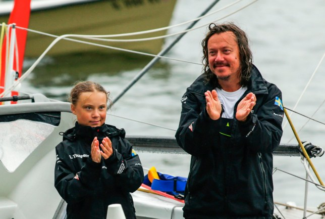 """Swedish climate activist Greta Thunberg, 16, and father Svante Thunberg arrive in the US after a 15-day journey crossing the Atlantic in the Malizia II, a zero-carbon yacht, on August 28, 2019 in New York. - """"Land!! The lights of Long Island and New York City ahead,"""" she tweeted early Wednesday. She later wrote on Twitter that her yacht had anchored off the entertainment district of Coney Island in Brooklyn to clear customs and immigration. (Photo by Kena Betancur / AFP) (Photo credit should read KENA BETANCUR/AFP via Getty Images)"""