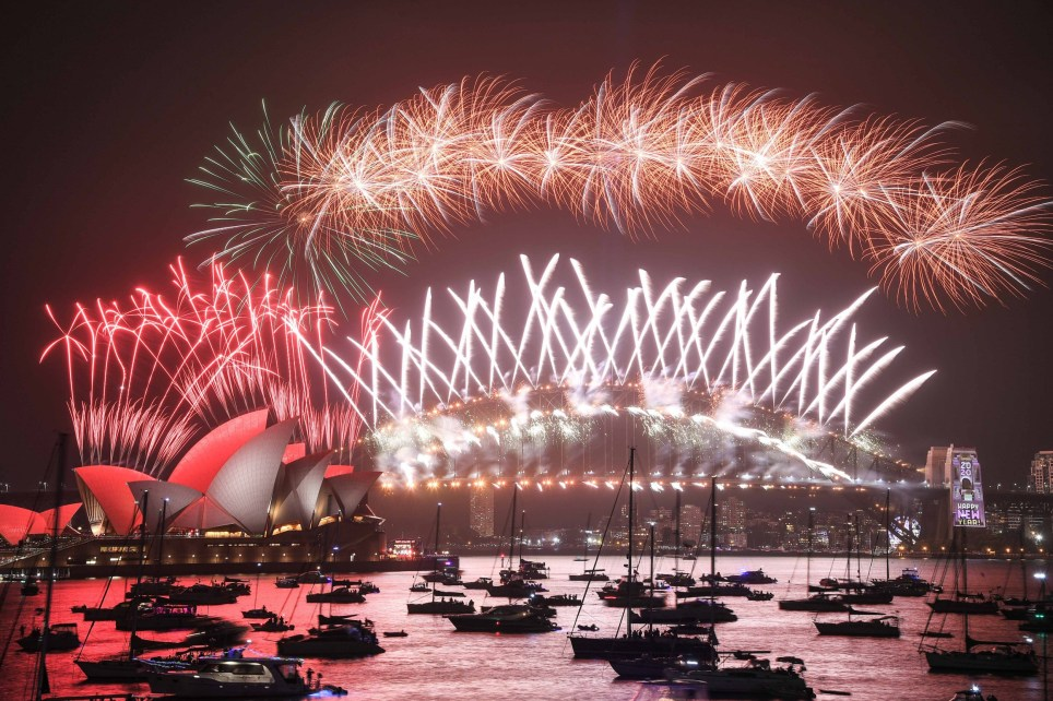 SYDNEY, AUSTRALIA - JANUARY 01: Fireworks explode over the Sydney Harbour Bridge and the Sydney Opera House in the midnight display during New Year's Eve celebrations on January 1, 2020 in Sydney, Australia. (Photo by James Gourley/Getty Images)