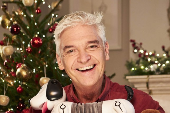 Philip Schofield holds a toy dog and smiles to camera.