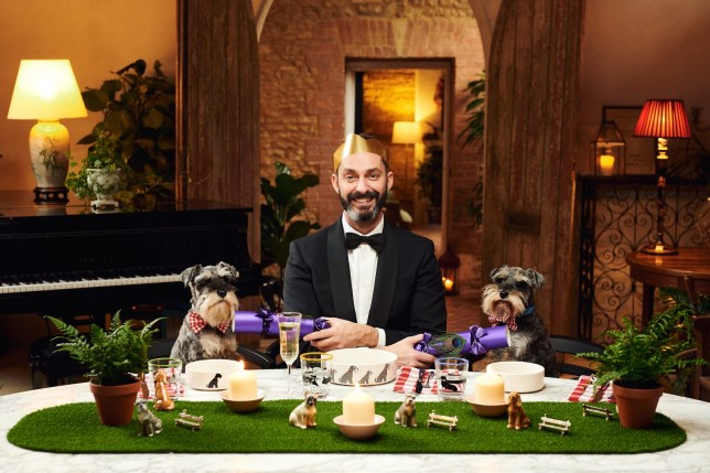Dylan Watkins from Poppy's Picnic sat at a table with two schnauzers, holding Christmas crackers